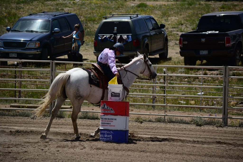 horse and rider riding around a barrel